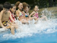 Small children sitting on edge of pool splashing water