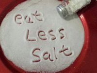 "Plate of salt with phrase ""Eat Less Salt"" written in salt."