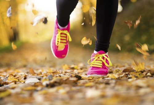 close up of woman's pink tennis shoes running with leaves falling.